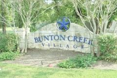 Sign at the entry to Kyle's Bunton Creek Village subdivision 78640